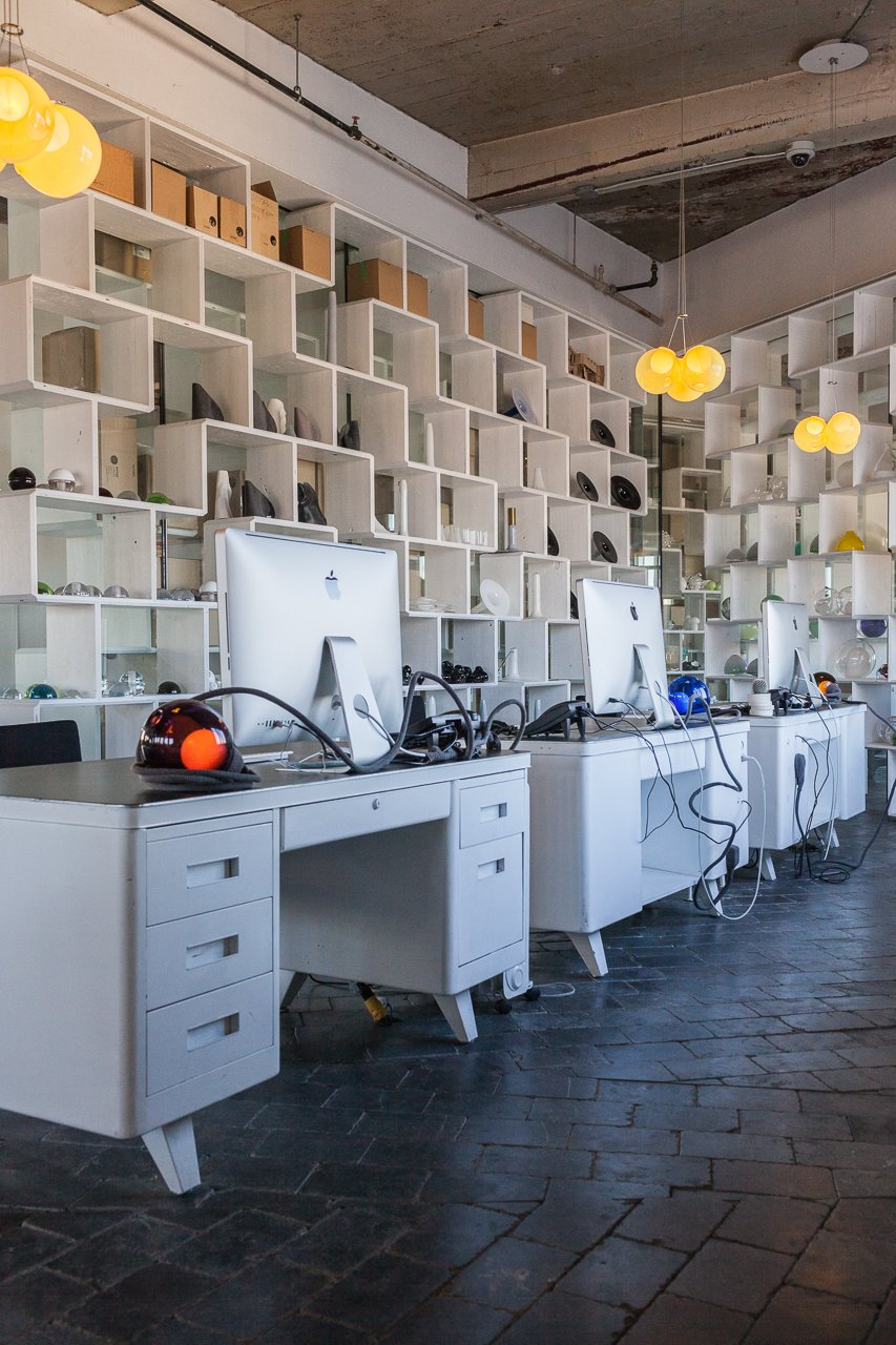 White metal desks are lit by a desk lamp variation from Bocci's 28-series. Behind them, open bookshelves act as room dividers.  Photo 5 of 8 in Inside the Head Office of Bocci