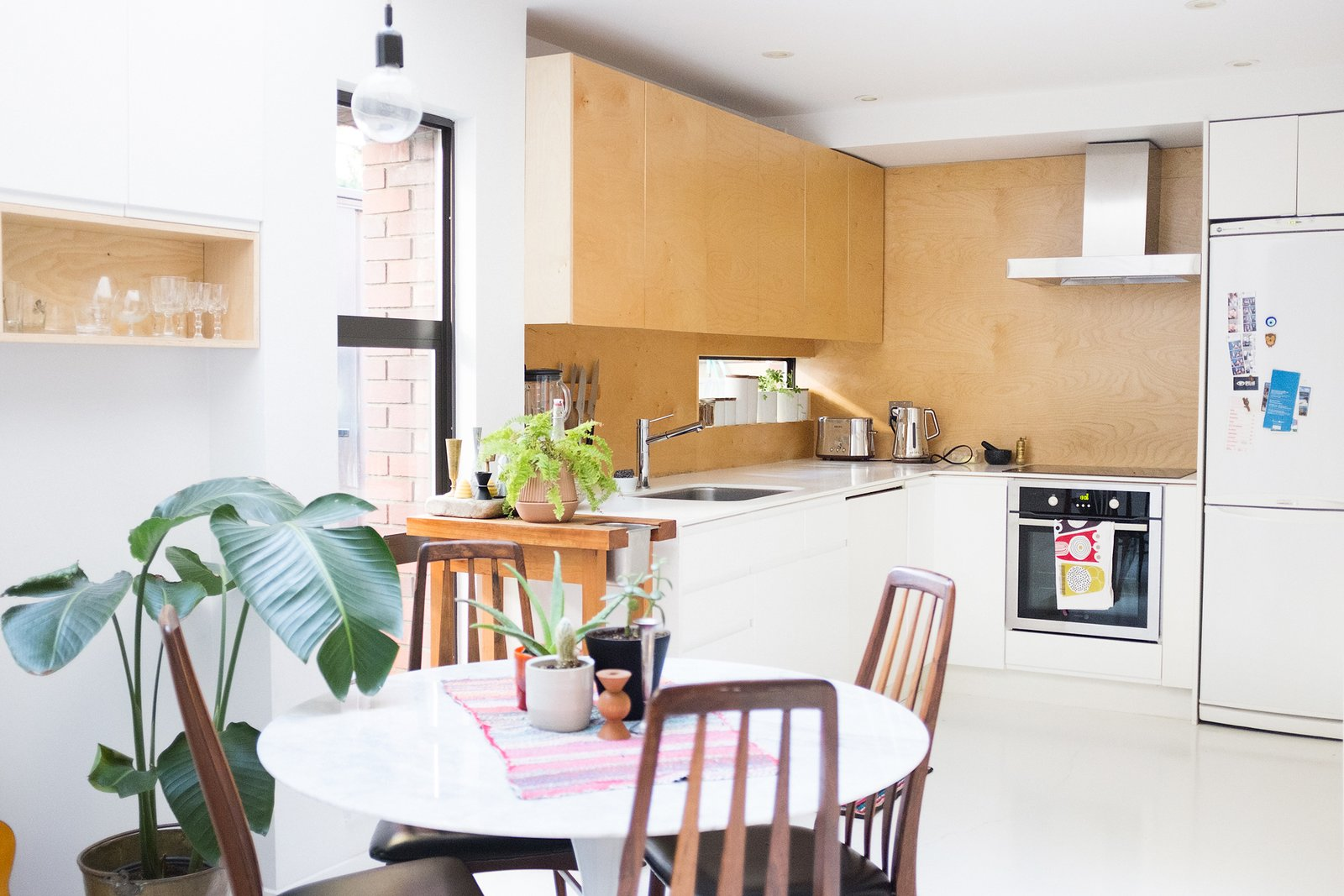 Kitchen, Concrete Floor, Wood Backsplashe, Range Hood, White Cabinet, and Wood Cabinet The open-plan kitchen is modernized with birch plywood cabinets, corian countertops and space-efficient appliances.  Photo 6 of 9 in A Revitalized Townhouse that Owes Everything to Angles