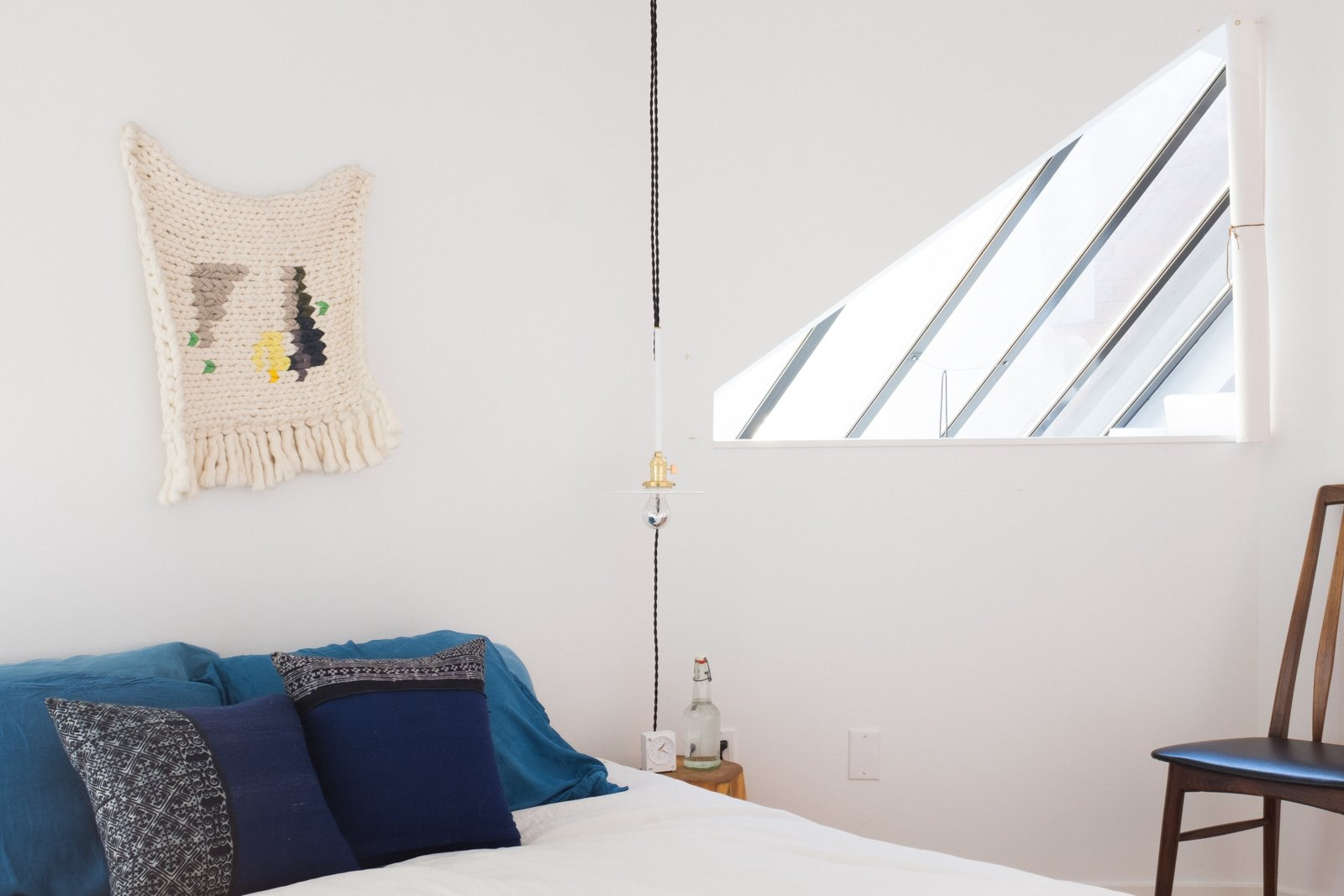 The triangle peek-hole in the bedroom allows light to pour in from the central skylight.  Photo 7 of 9 in A Revitalized Townhouse that Owes Everything to Angles