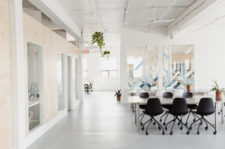 Werklab's shared desk areas, private offices on the left, and windows to the boardroom—with glass artwork by Yuli Glass. Svelti office chairs by Article.