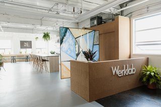 The entrance to Werklab features a custom cork-panel concierge and a hanging glass partition by Yuli Glass—who create permanent glass art using ceramic pigments, tempered glass, and industrial kiln firing in a patent-pending process.