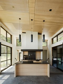 Warm wood and dark surfaces contrast with white walls.