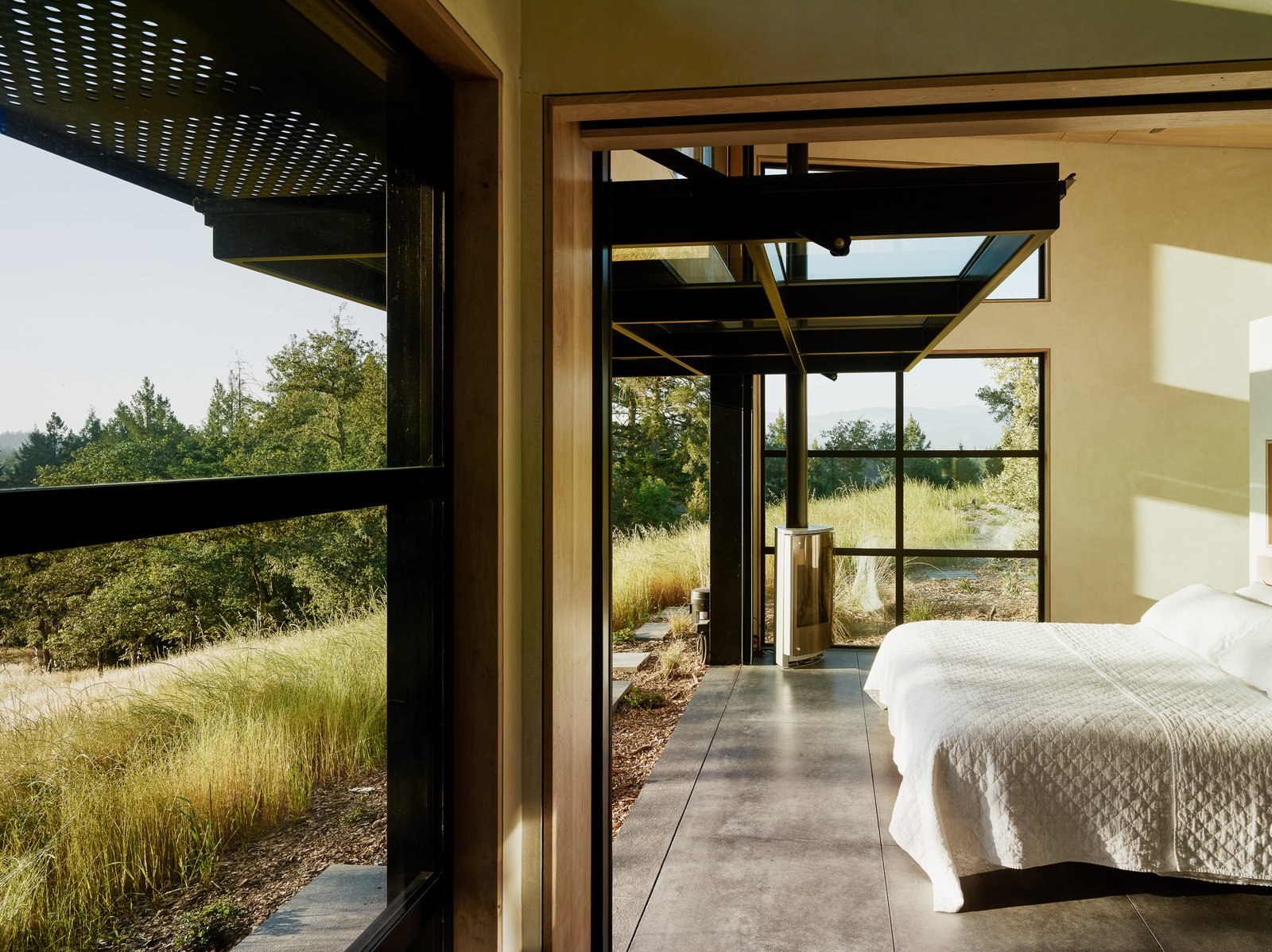 Bedroom, Bed, and Concrete Floor Even the bedrooms are just a few steps away from nature.  Photo 7 of 10 in Four Enormous Glass Doors Turn This Northern California Home Into an Outdoor Pavilion from Sonoma Wine Country I
