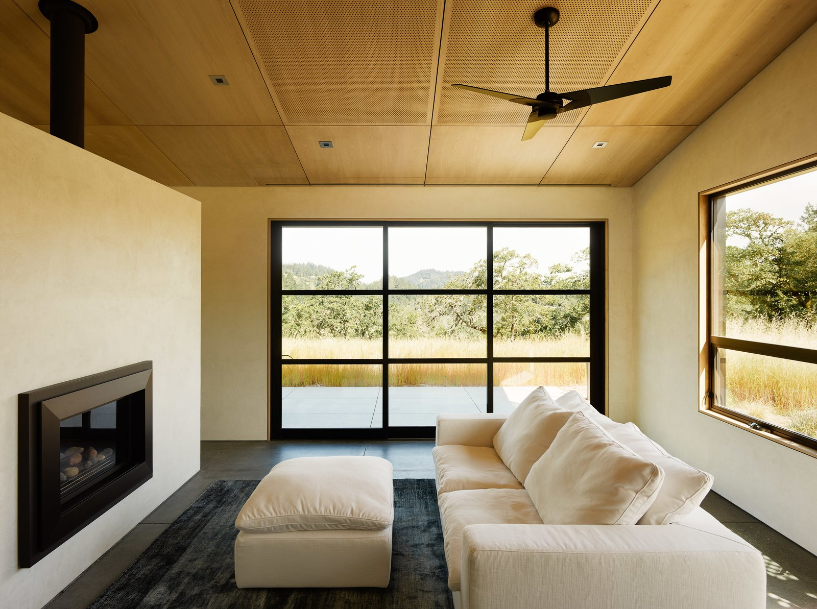 Living Room, Concrete Floor, Standard Layout Fireplace, Recessed Lighting, Sofa, Rug Floor, and Ottomans Neutral furnishings and gray floors don't distract from the views.  Photo 10 of 10 in Four Enormous Glass Doors Turn This Northern California Home Into an Outdoor Pavilion from Sonoma Wine Country I