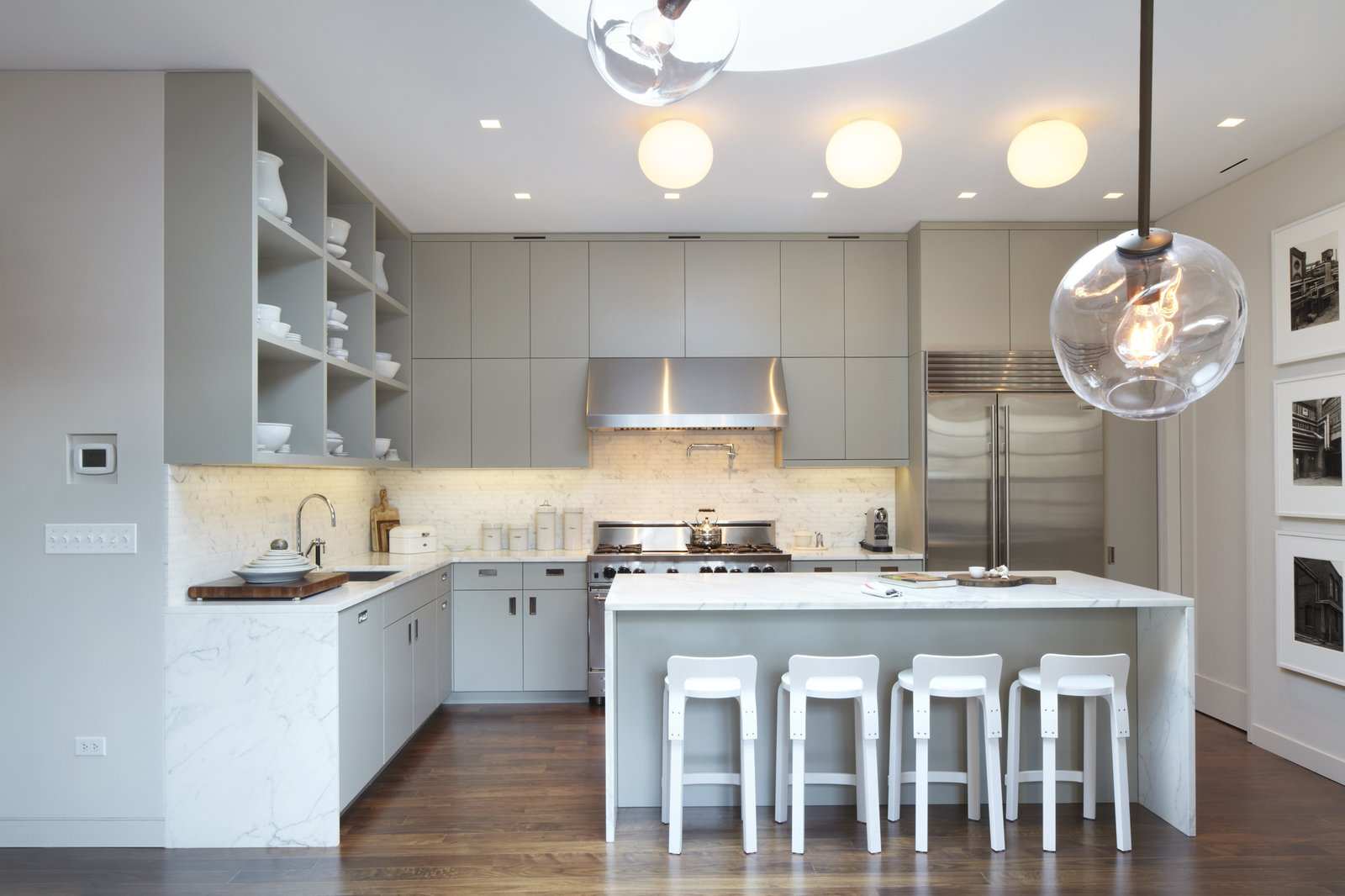 An overall photo of the kitchen with the Bernd and Hilla Becher photograph series on the right.  The drum skylight can be seen above and in the foreground are branches of a Lindsey Adelman pendant which hangs over the dining table.  White Street Residence by pulltab