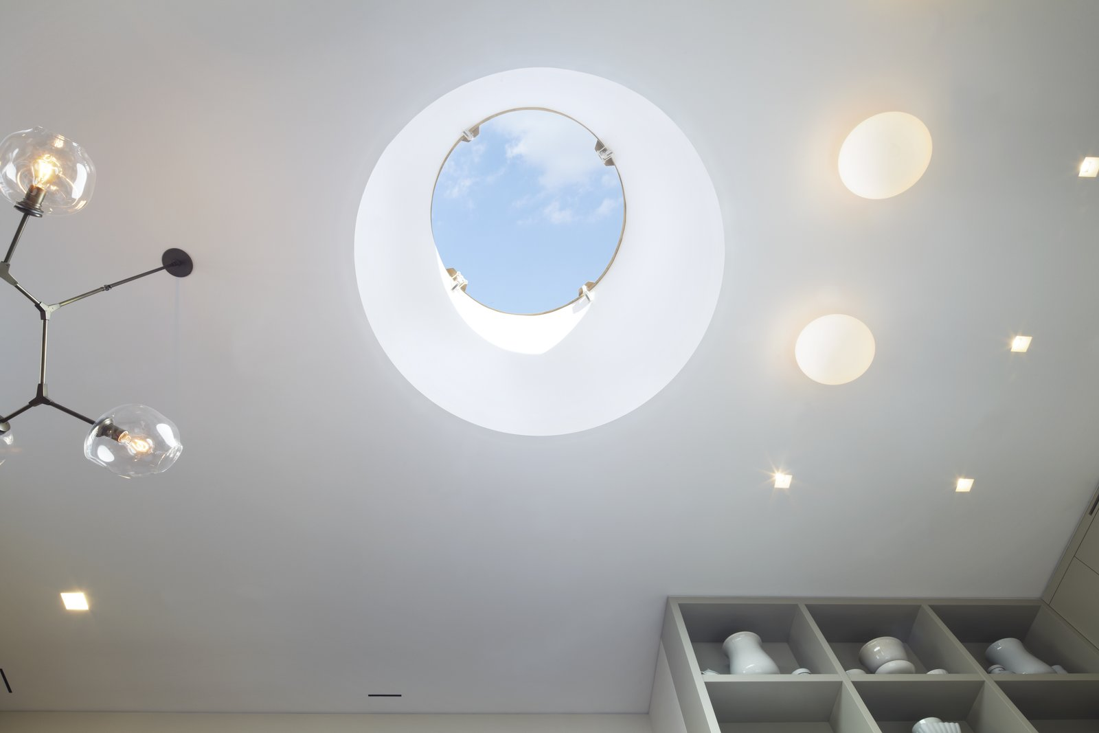 Looking up into the 5' wide drum skylight in the White Street Residence - remote controlled synchronized linear actuators open and close the skylight which allowed us to meet the NYC Code for legal light and air.  A beautiful Lindsey Adelman Branch chandelier is on the left and Flos Glo Ball fixtures paired with USAI Bevel trimless fixtures are on the right.  White Street Residence by pulltab