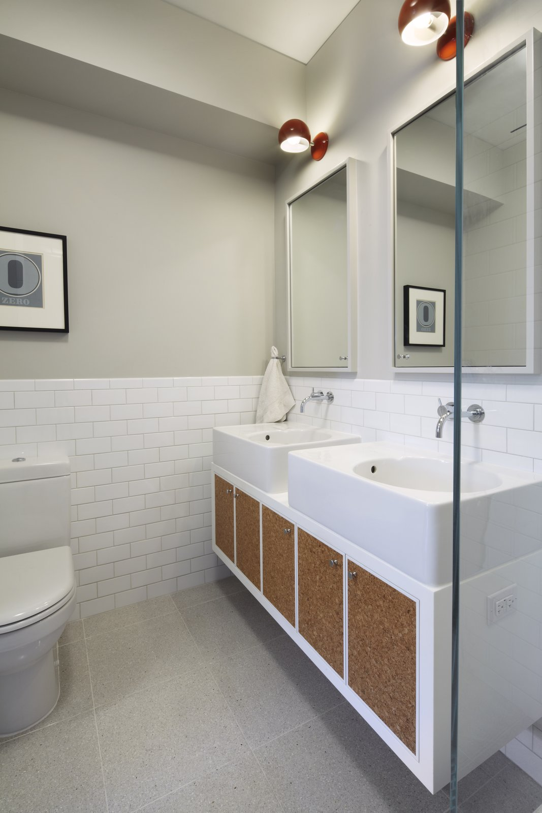 A photo of the double vanity in the children's bathroom.  The vanity was custom made from Corian with Scola sinks from Duravit and one of our favorite faucets from Vola designed by Arne Jacobsen.  The inset panels are natural cork with a wax finish.  White Street Residence by pulltab