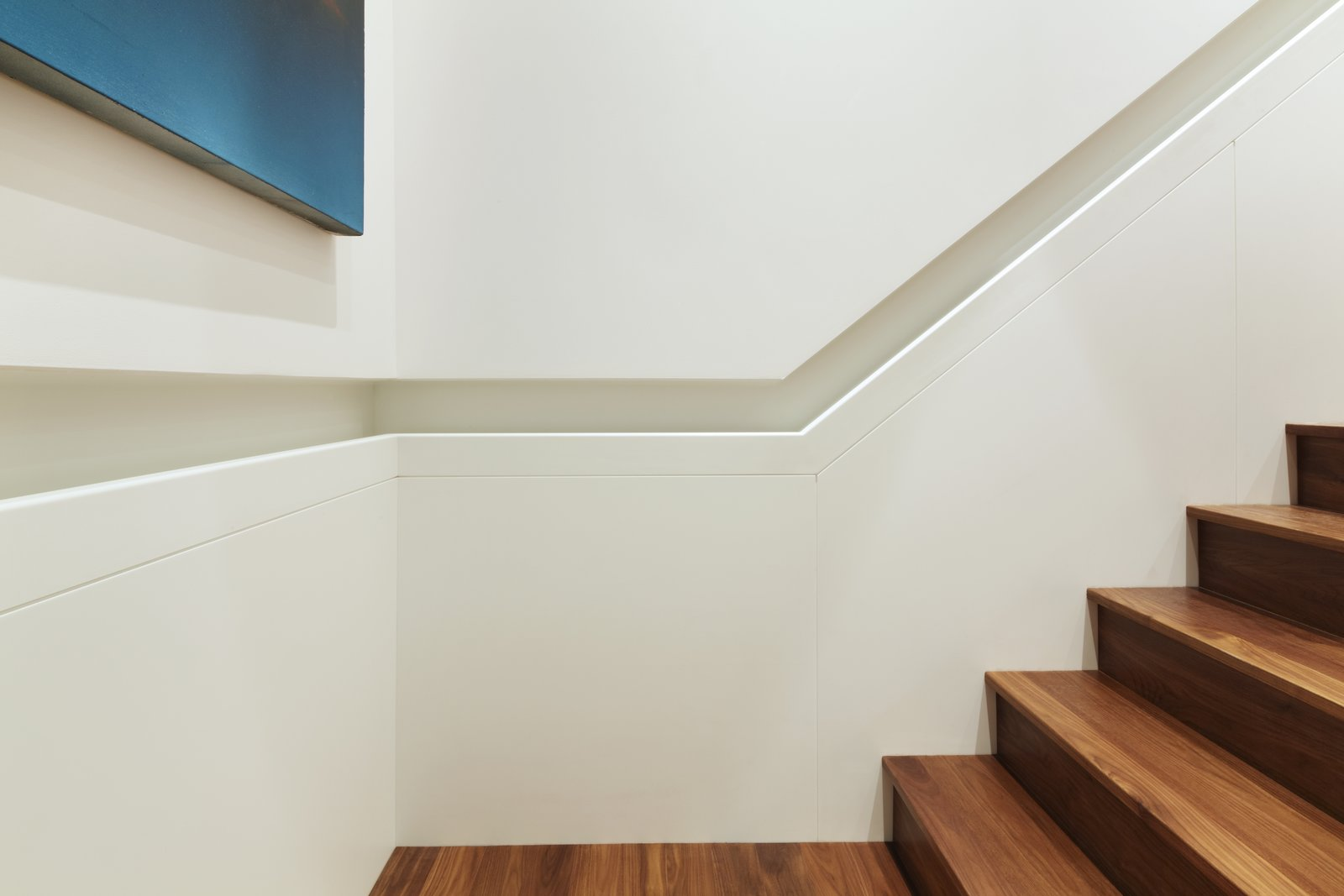 A detail photo of the inset handrail.  The lower panels and handrail are fabricated from Glacier White Corian - above the handrail is skim coated drywall painted to match.  The handrail runs continuously from the lower floor to the penthouse.  White Street Residence by pulltab