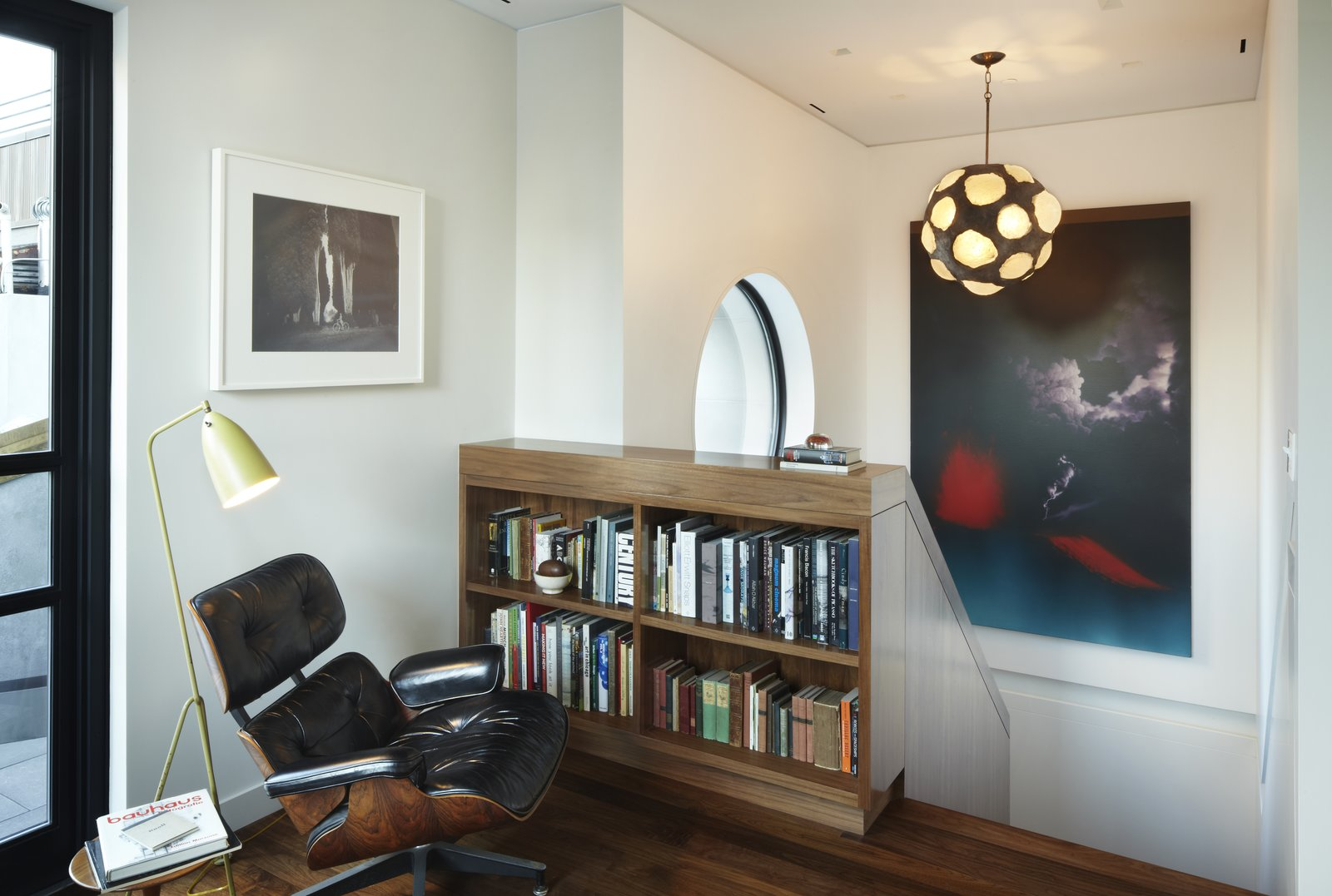 The upper landing in the White Street Residence provides a pausing point when going to and from the roof garden.  A walnut bookshelf, an extension of the walnut knee wall below stores a collection of the owner's art books.  The large circular window which overlooks the roof garden can be seen in the background. A vintage Grasshopper floor lamp by Greta Grossman provides reading light while relaxing in the Eames 670 lounge chair.  White Street Residence by pulltab