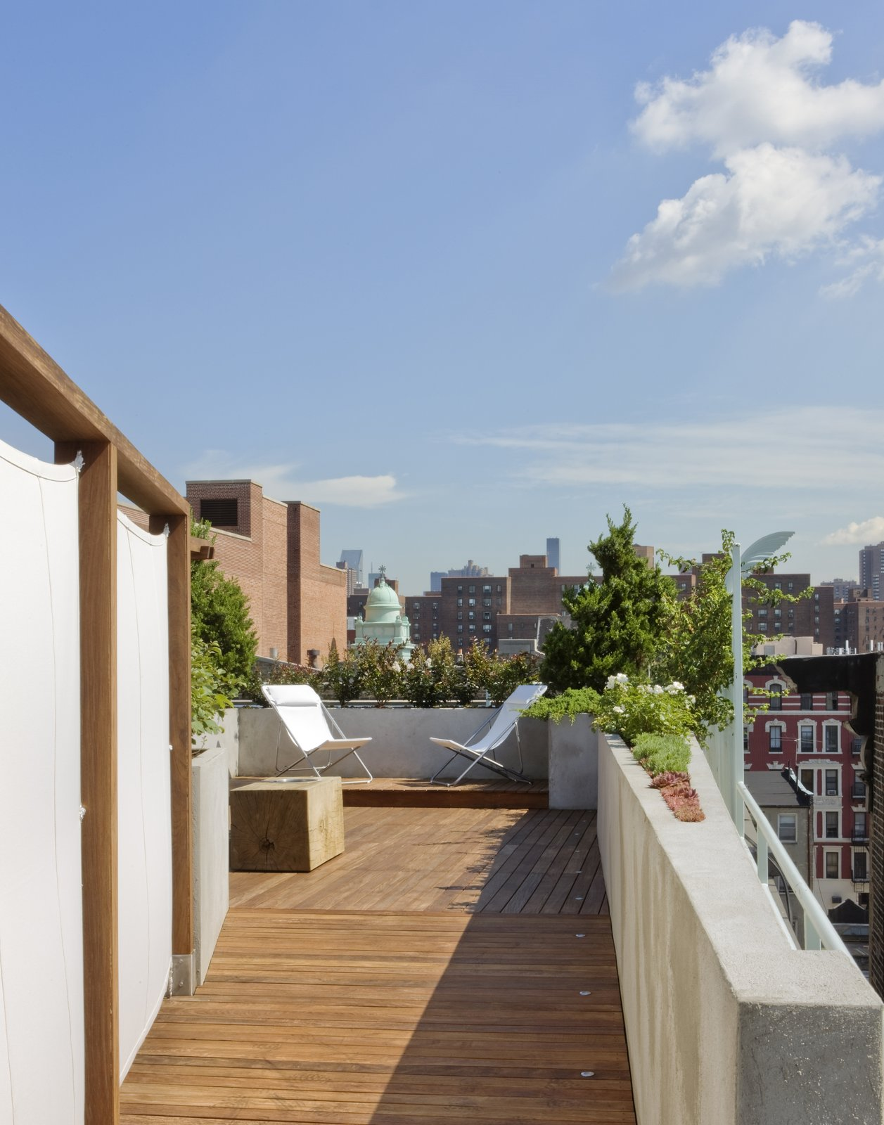A view from the connecting ramp towards the upper level of the roof deck.   A custom Portland cement stucco planter wall tapers in a wedge shape continuing the line of the building parapet.  Military surplus canvas screens are on the right.  These are removable allowing access to existing service areas on the roof.  East Village Roof Garden