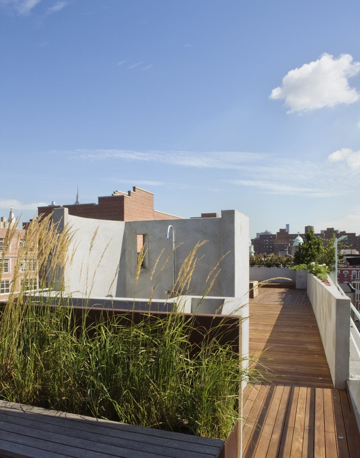 A view from the entry to the roof deck toward the outdoor shower.  The shower wall has an opening which frames the New York Life Insurance Building which can be seen in the distance.  East Village Roof Garden