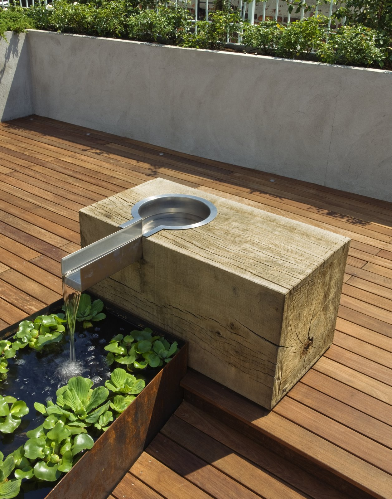 The oak block was sourced from a mill outside of Philadelphia.  The block was rough sawn and left unfinished to weather and develop a patina.  The lined water trough is fabricated from Cor-Ten steel.  East Village Roof Garden
