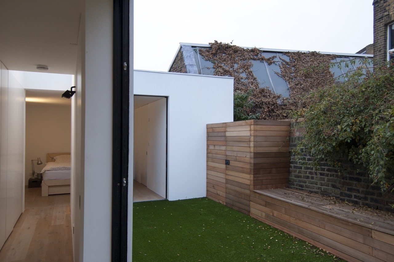 The master bedroom and bathroom can be viewed across the courtyard from the galley kitchen that occupies the glazed link.  Unité de Rénovation