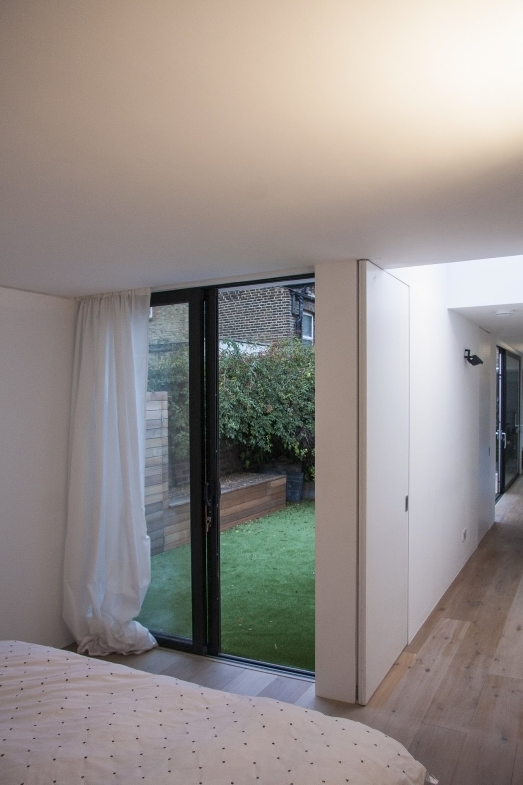 From the master bedroom one can look back down the length of the space through the internal kitchen link or the external courtyard.  Unité de Rénovation