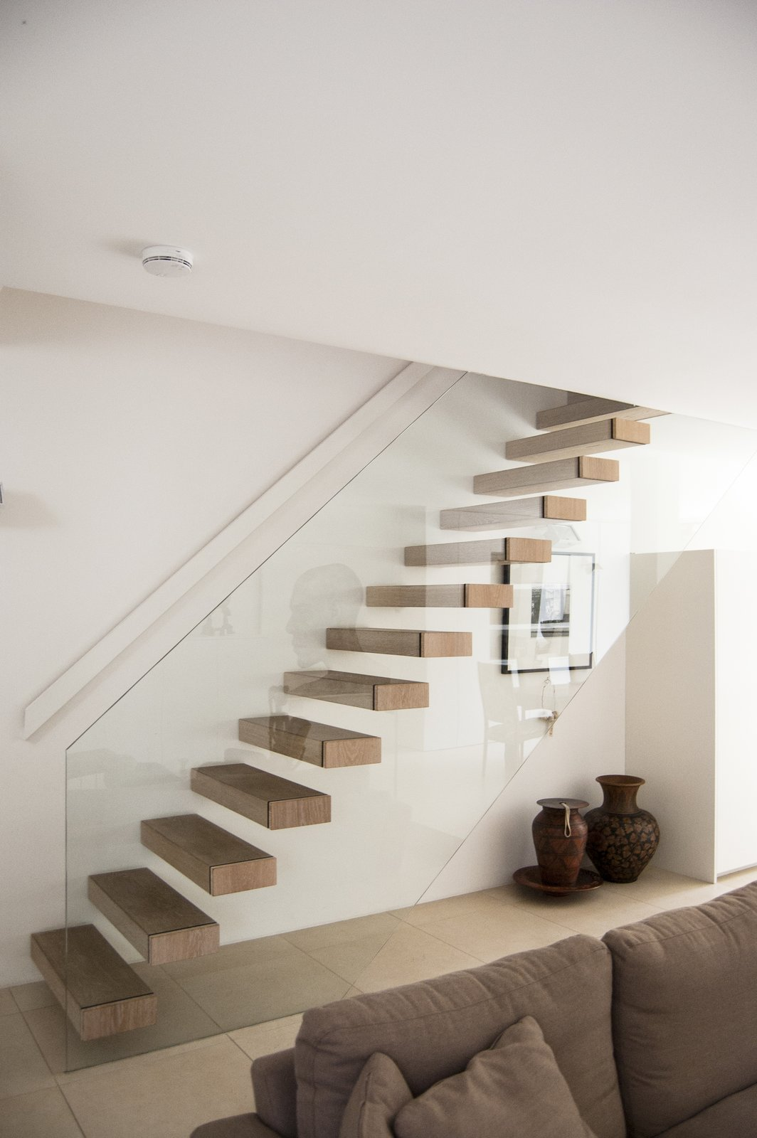 Glass Railing, Wood Tread, Living Room, Ceramic Tile Floor, and Sofa Living and dining spaces are open-plan to the kitchen and courtyard, all of which share a continuous, tiled floor finish.  Soupçon Brut by WILLIAM TOZER Associates