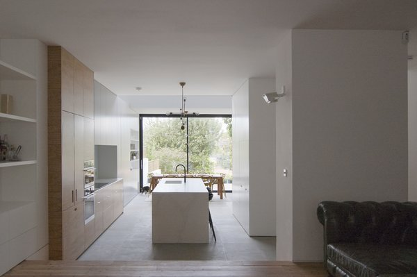 The spaces are further delineated by large, white sculptural volumes, which define soft edges between them while providing storage. The kitchen is articulated as a composition of smaller-scale volumes variously finished in stone, timber veneer, and white paint.