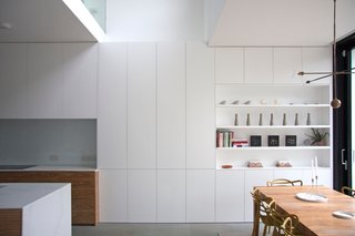 The open-plan kitchen and dining space is punctuated by a double-height space, which loosely divides the two zones of use.