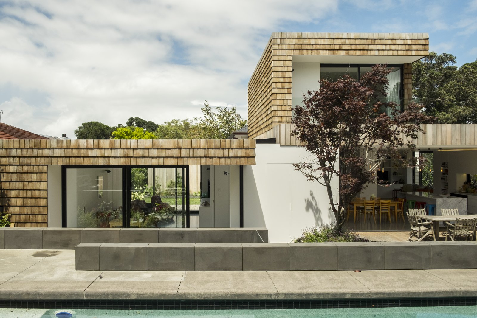 Viewed from the swimming pool, the new scheme largely obscures the original house—appearing as a new-build, modern house of a composition reminiscent of the mid-twentieth-century Case Study Houses.