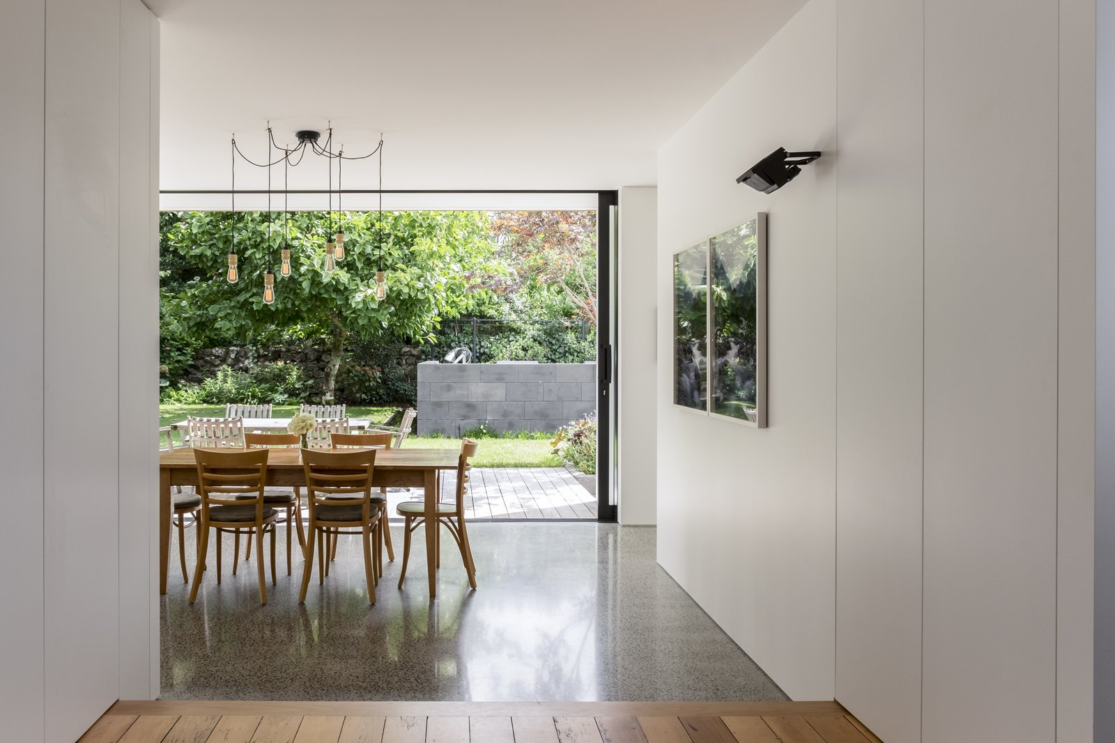 Kauri flooring to the raised living area delineates the living space, while the kitchen and dining spaces are defined by a diamond-ground concrete floor, lowered to be level with the timber decking to the adjacent courtyards.