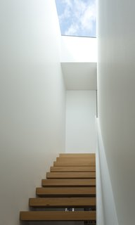 The form of the top-lit, kauri-clad, open-riser staircase references the drawn appearance of a staircase, and recalls the Stack works of the American artist Donald Judd.