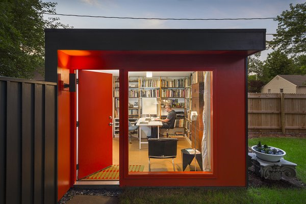 This detached home office unit by FORWARD Design | Architecture features a fire engine red exterior and ample storage within.