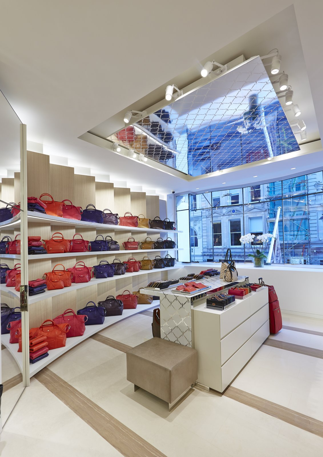 Lacing reminiscent of Longchamp's LM motif appears across ceiling tiles, wall panels, and product display stands, tying the space together.  Photo 5 of 5 in Mural Artist Sets the Scene at Longchamp's Flagship Store in London