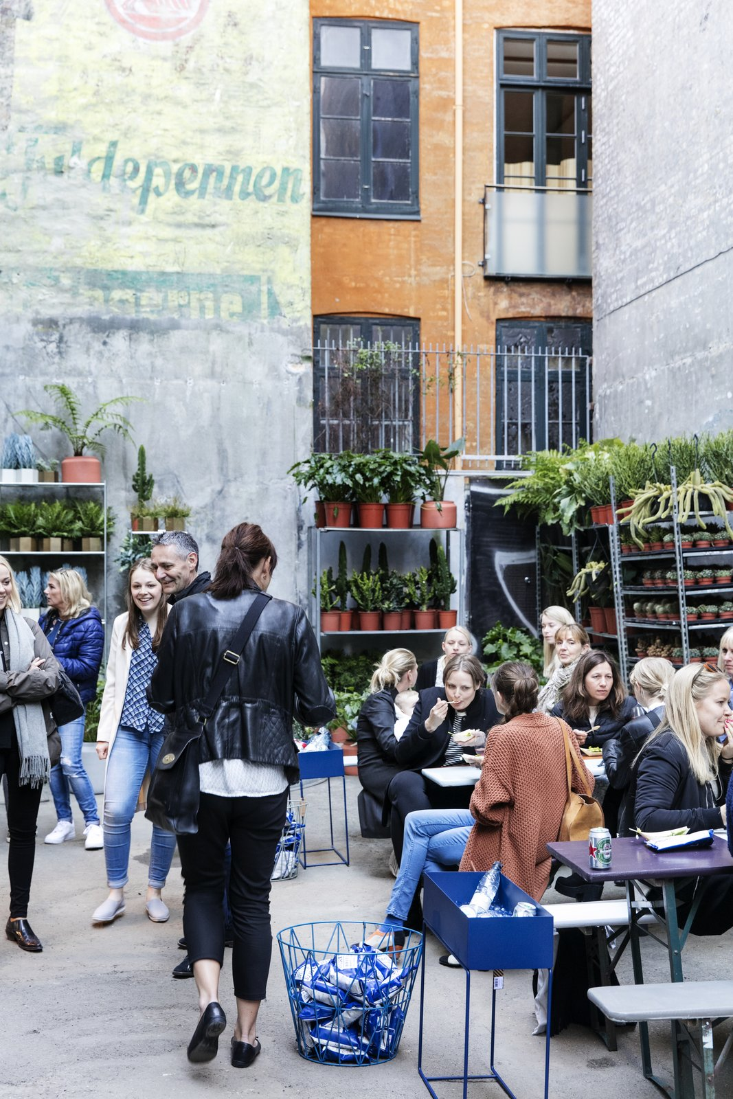 A plant shop occupies a section of the courtyard, where shop visitors can gather over coffee, pastries, ice cream, and more.  Photo 5 of 5 in A Retired Copenhagen Power Plant Hosts a Design Pop-Up