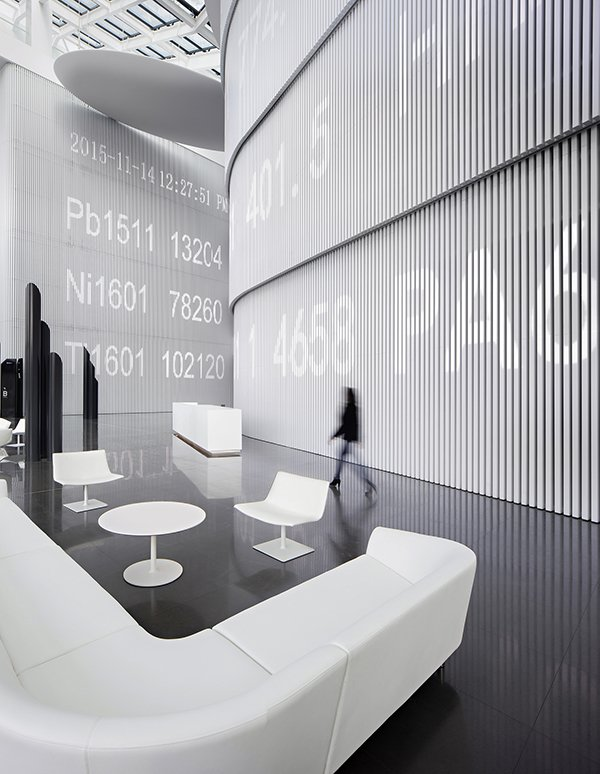 A ticker runs along the wall, superimposing digitally the work done in physical space.  Photo 3 of 4 in Chinese design firm Hallucinate created a futuristic office for Maike Group