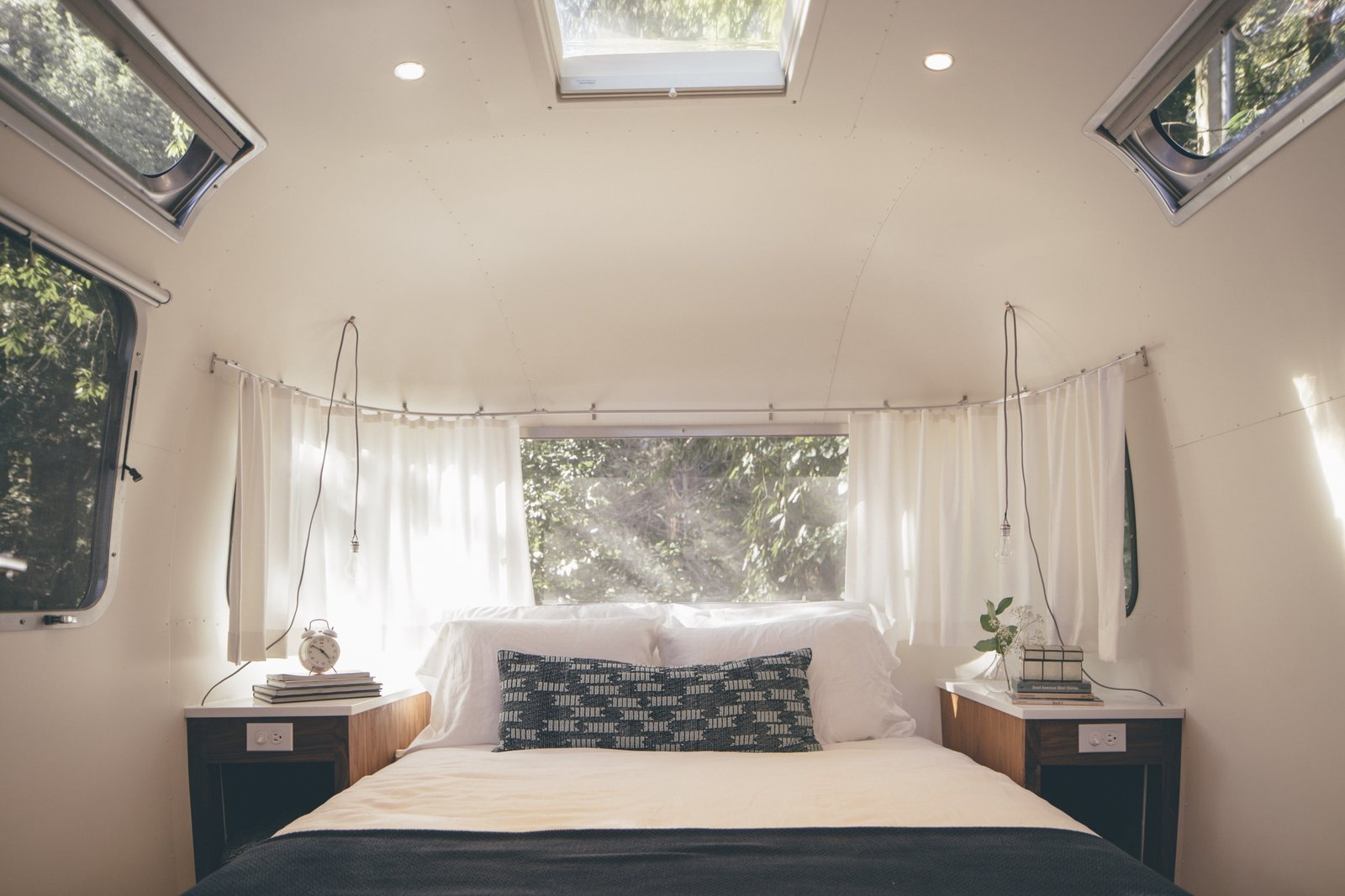 Airstream suites include queen-sized Casper mattresses with deluxe bedding. The pendant lights are from Schoolhouse Electric.  Photo 4 of 7 in AutoCamp's Modern Clubhouse Emerges from the Russian River Redwoods