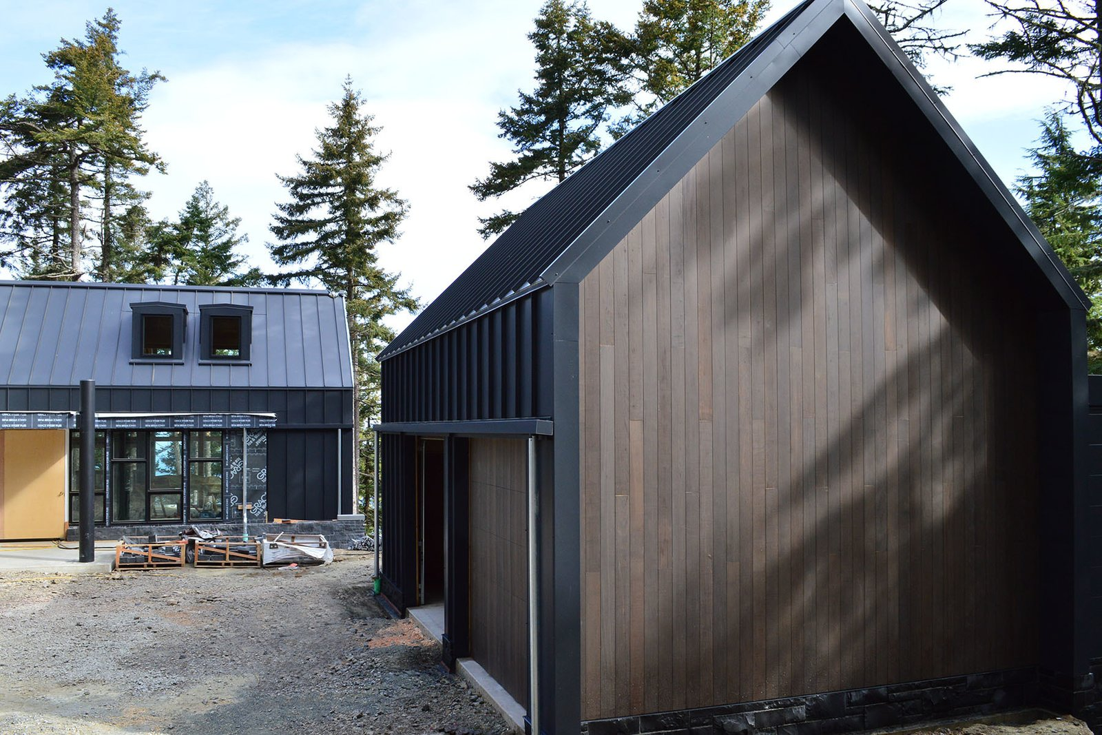 The garage exhibits the same black steel cladding and stained cedar siding as the main structure. Flat dormer windows on the house provide natural light and add visual interest to the overall shape.  Photo 2 of 5 in Paint it Black: One Couple's Journey to Minimalism