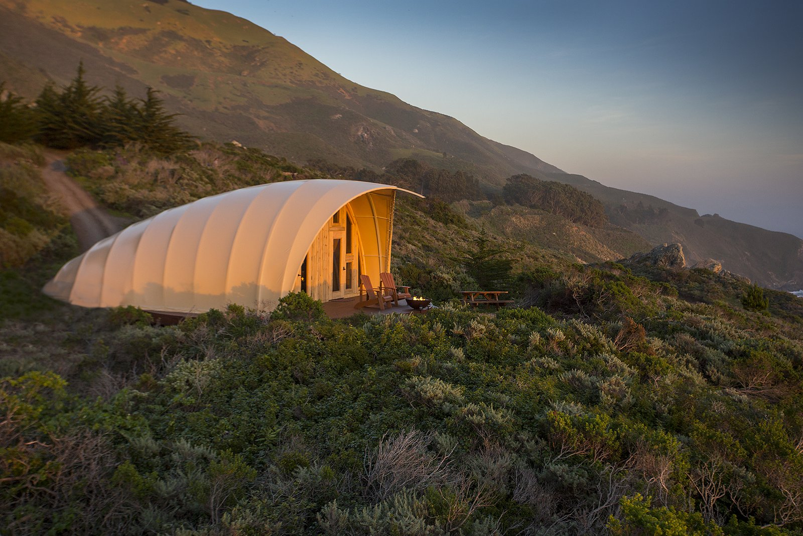 Outdoor, Grass, Small Patio, Porch, Deck, Trees, Slope, and Shrubs The Autonomous Tent is available to book for $495 plus tax per night. To make a reservation, visit the Treebones Resort website.  Photo 5 of 5 in Sleep in a Translucent Cocoon for $495 a Night