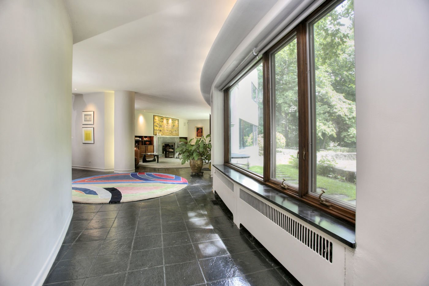 A meandering corridor connects the dining room and living room. Labatut notes that  Photo 4 of 9 in A Curvaceous Connecticut Home Asks $2.6M