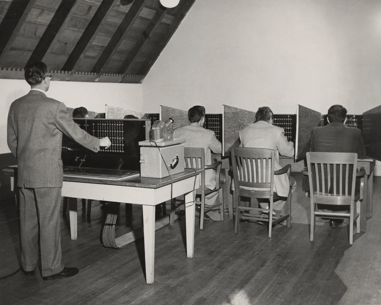 Researchers simulate the Conformity Test. In this scenario, five subjects in private booths estimate distances after a light indicates the other participants' answers—the supplied answers are fake, however, allowing this test to measure the effect of peer pressure on judgment. While Victor Lundy saw through the deception, others deferred to the false responses.  Photo 5 of 14 in This Book Unearths a Midcentury Personality Study on Architectural Giants