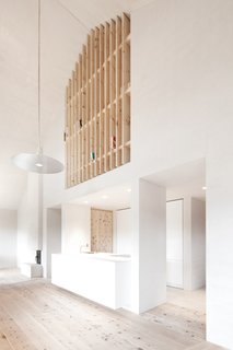 Upstairs, a wooden slatted wall doubles as a bookshelf.