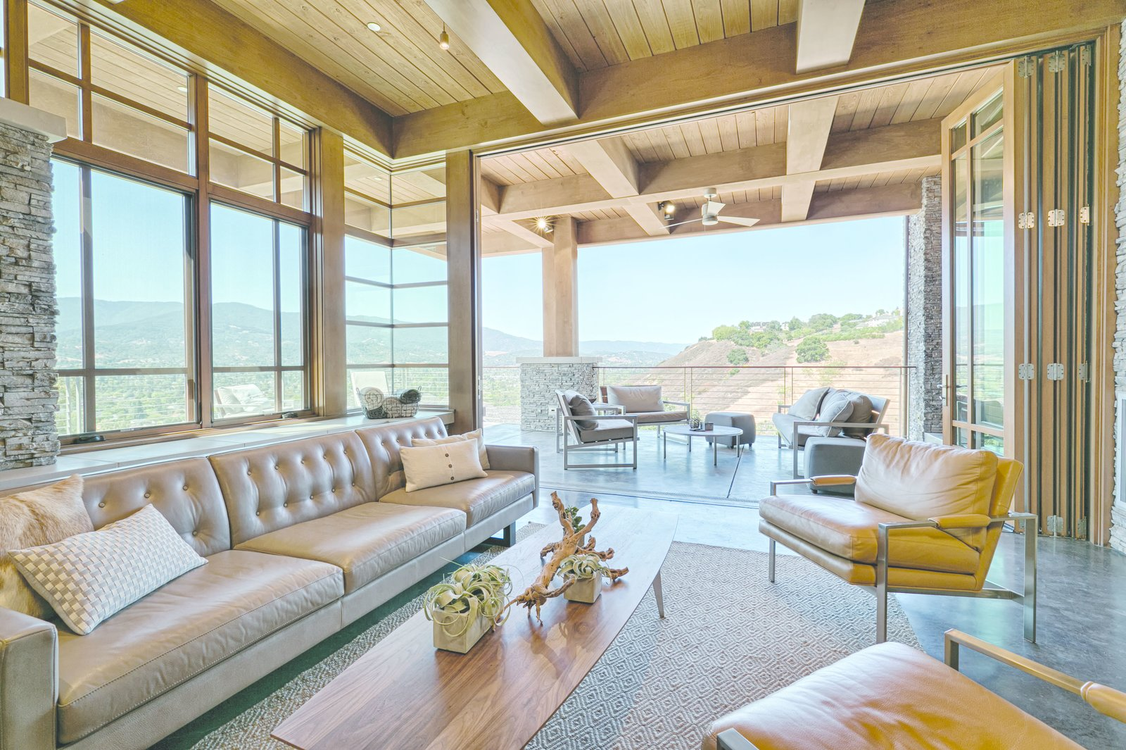 The glass walls of the living room fold back to create uninterrupted space between indoors and outdoors.  Photo 5 of 9 in An Architectural Feat in Silicon Valley Tames a Rocky Landscape