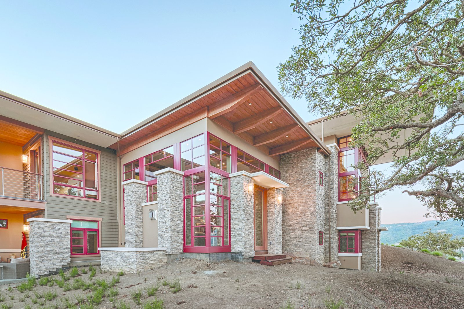 The home rises and falls across 7 levels to accommodate the contours of the site. While the exterior dry stacked stone, cedar siding, and wood trim echo the natural landscape, the red windows lend contrast and definition.  Photo 9 of 9 in An Architectural Feat in Silicon Valley Tames a Rocky Landscape