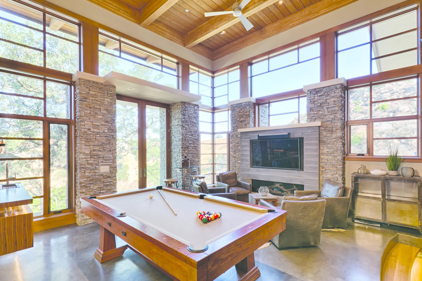 From the living room, thick oak stair treads suspended on steel stringers descend to the game room, where a walnut bar, Craftsman pool table, and fireplace set the scene for entertaining and lounging.  Photo 8 of 9 in An Architectural Feat in Silicon Valley Tames a Rocky Landscape