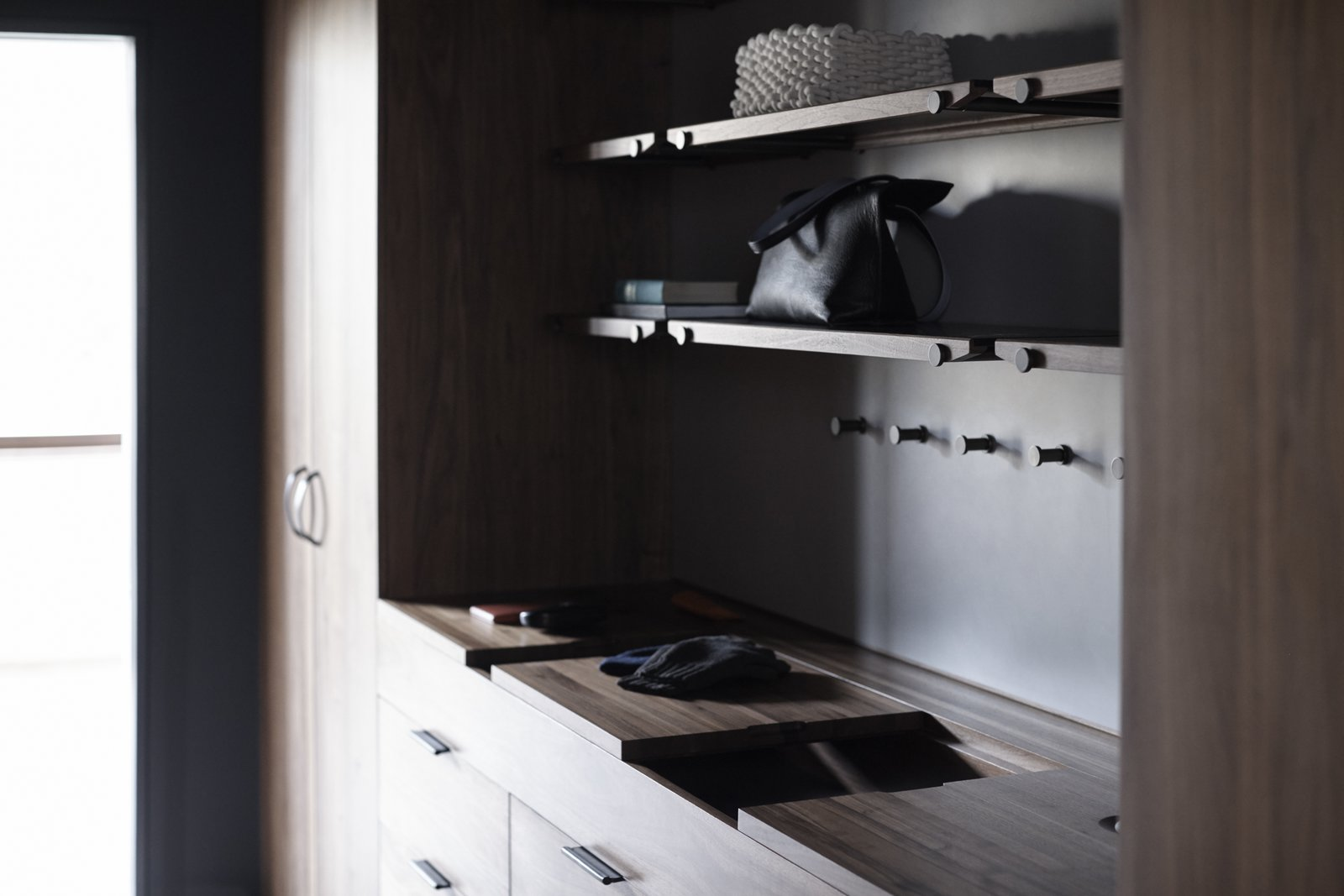 The Wardrobe System features sliding wooden valet trays, leather lined storage compartments, custom interior felt door pockets, handcrafted leather pulls, and an integrated laundry hamper.  Photo 8 of 9 in The Whole House System That Unifies Every Room