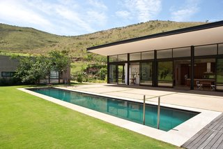 The pool stretches across a rolling lawn that ends at the foot of the wooded mountains.