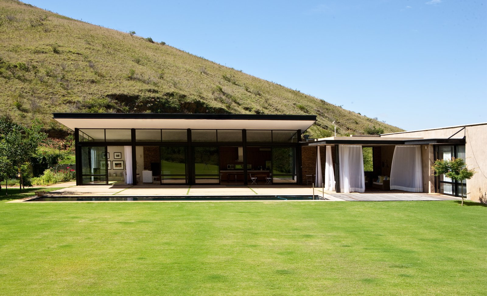 Outdoor, Grass, Back Yard, Large Patio, Porch, Deck, and Shrubs Herman and van Gass chose only natural materials like glass, steel, and stone, and designed the house to harvest its own water supply.  Photo 2 of 9 in This South African Villa Lets You Bask in Divine Views