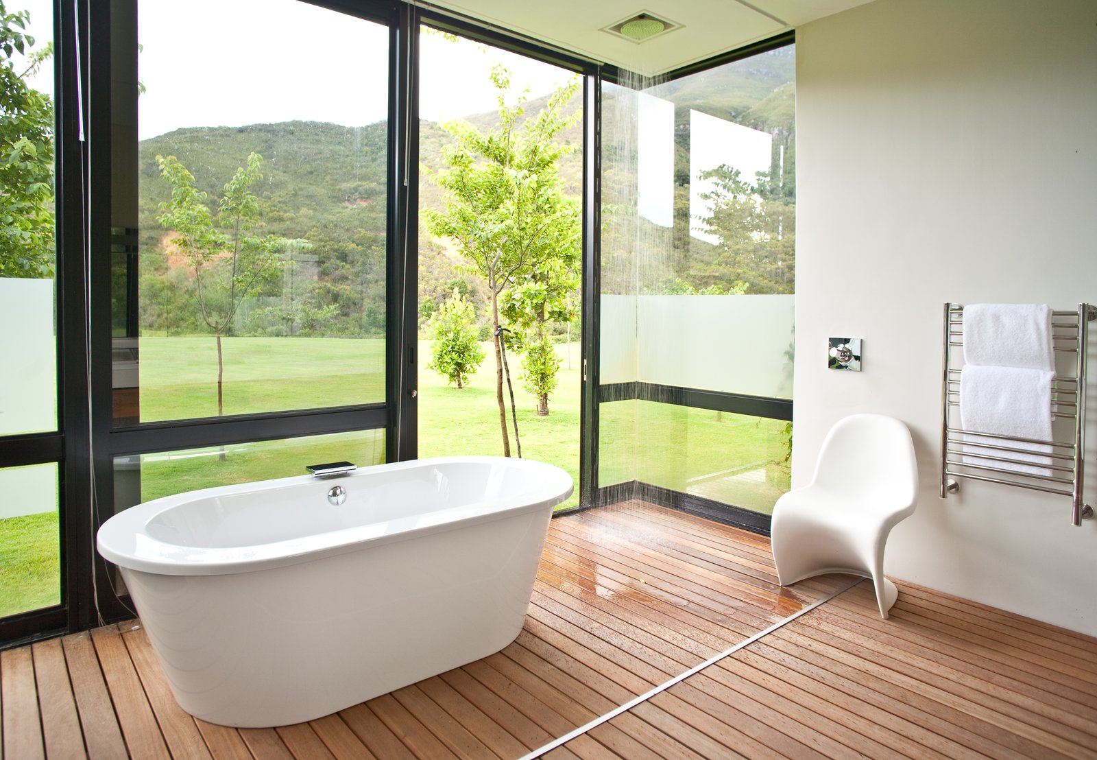 Bath Room, Open Shower, Medium Hardwood Floor, Soaking Tub, and Freestanding Tub The guest bathrooms are outfitted with showers and tubs that feel close to nature.  Photo 6 of 9 in This South African Villa Lets You Bask in Divine Views