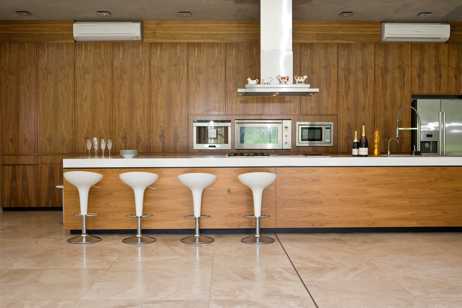 Kitchen, Refrigerator, Range, Ceiling Lighting, Microwave, and Range Hood Herman and his wife love to cook for and entertain their guests. They also have a great selection of South African wine and malt whiskey.  Photo 4 of 9 in This South African Villa Lets You Bask in Divine Views