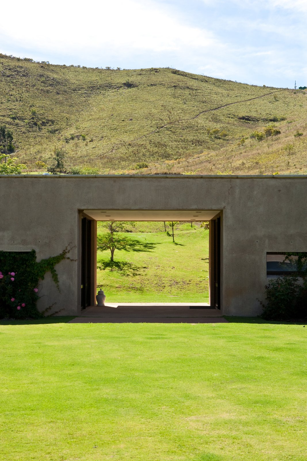 Outdoor, Back Yard, Grass, Shrubs, Trees, and Slope Herman describes the shape of a sleeping dragon nestled in the mountains. In keeping with a Feng Shui philosophy, he intentionally left a hole in the building to allow the beast a clear view.  Photo 7 of 9 in This South African Villa Lets You Bask in Divine Views