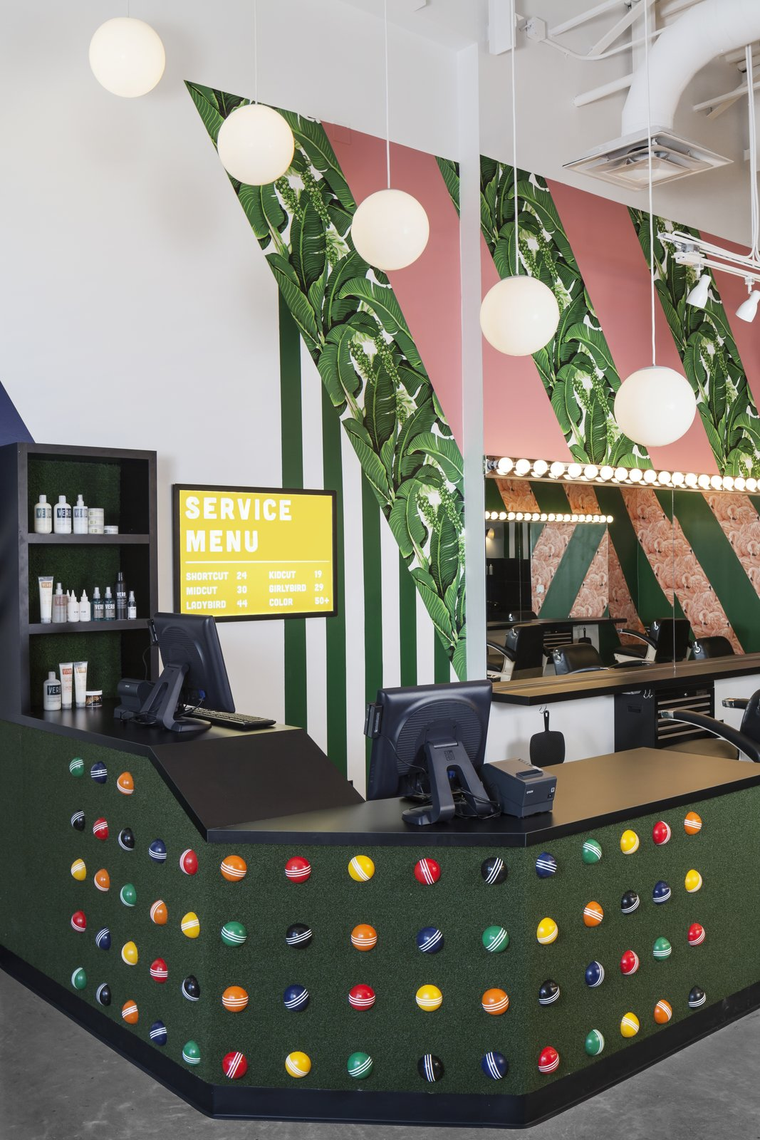 Artificial turf and croquet balls add texture and personality to the reception desk.  Photo 5 of 7 in A Barbershop That's a Cut Above