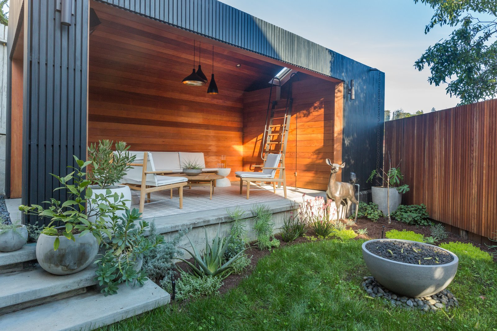 The minimalist garage takes the form of an archetypal house. The gutters and weather- and waterproofing are concealed by redwood slats that can be removed for future repairs. Black Pine Tar coats the rainscreen, creating a striking contrast to the warm interior.  Photo 12 of 15 in No Longer Off-Kilter