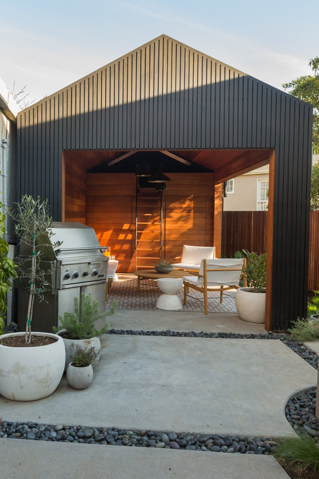 Garage, Garage Conversion Room Type, and Living Room Room Type Awkwardly shaped and saddled with a run-down garage, the backyard posed a challenge. Since the city wouldn't allow for the removal of the garage, Wendi and Lukas decided to convert it into additional living space.  Photo 23 of 25 in 25 Blissful Backyards from No Longer Off-Kilter