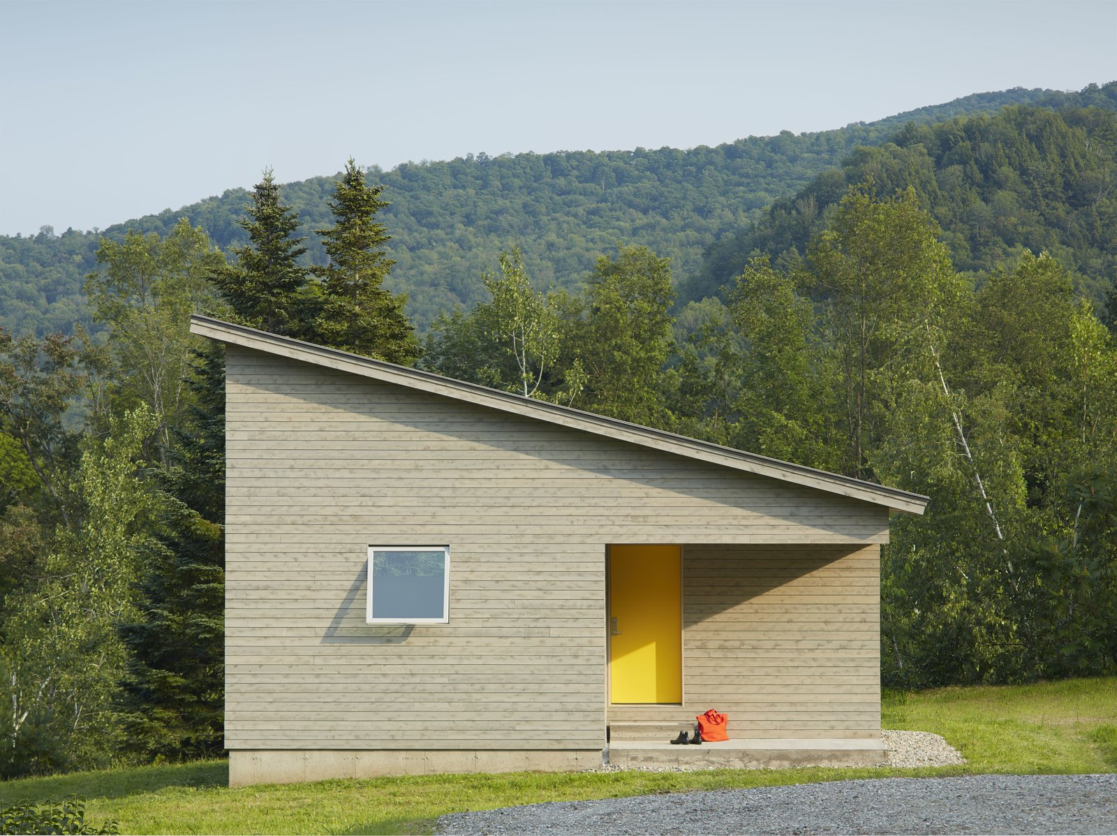 Exterior, Cabin Building Type, and House Building Type A cutaway in the structure's cubic shape forms a front porch, where a graphic yellow door welcomes visitors. The roof slopes downwards, holding more intimate spaces at its lower end.  Photo 2 of 5 in A Mini-Home With Mega-Views