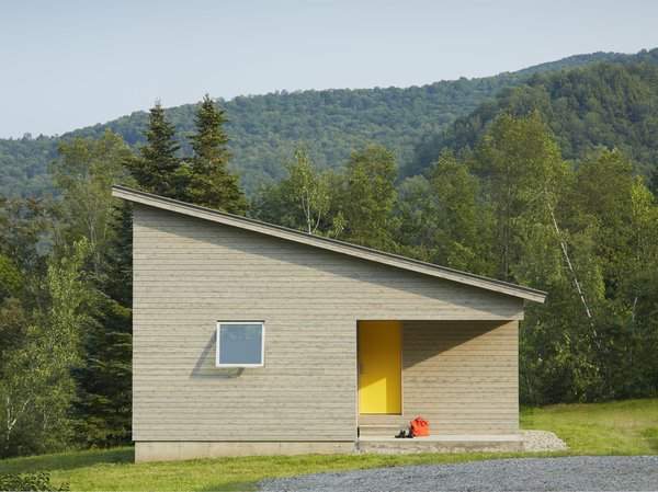 A cutaway in the structure's cubic shape forms a front porch, where a graphic yellow door welcomes visitors. The roof slopes downwards, holding more intimate spaces at its lower end.