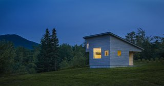 Built to stay cozy through all kinds of weather, Micro House has a gray-stained, cedar rain screen in addition to Lo-E glass. At a diagonal from the front porch, another subtracted corner makes space for a sleeping loft.