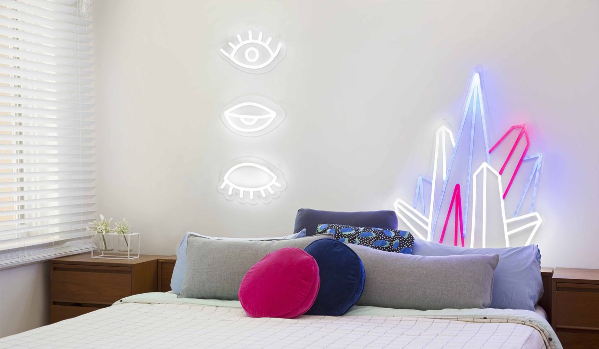 Eye! Eye! Eye! ($449) and Crystal Prism ($449) decorate a bedroom. Electric Confetti's designs come with a remote control that allows you to dim the neon to less than 5% brightness, ideal for a nightlight, or set it to an adjustable flashing speed.  Photo 4 of 8 in Next-Generation Neon